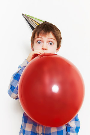 6 9 years: Boy blowing up balloon