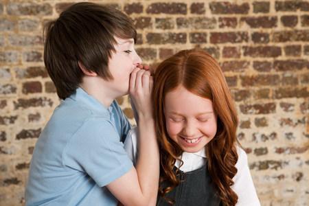 Boy whispering to girl LANG_EVOIMAGES