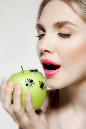 revulsion: Young woman eating apple with flies on it LANG_EVOIMAGES