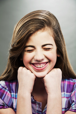 Portrait of young teenage girl laughing with eyes closed