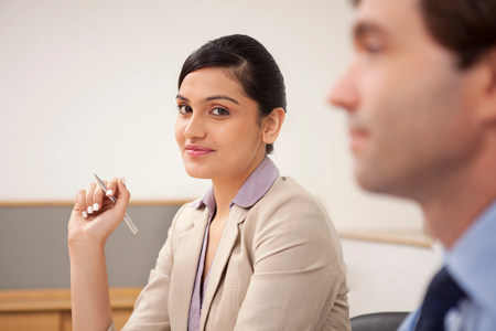 Portrait of a female executive in a meeting LANG_EVOIMAGES