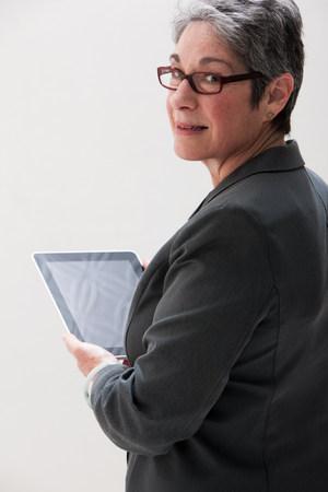 60 65 years: Mature businesswoman using digital tablet,studio shot LANG_EVOIMAGES