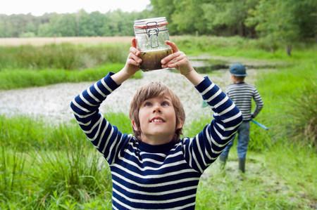 quizzical: Boy looking at tadpoles in jar