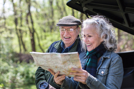 Senior couple reading map while sitting on car trunk in forest LANG_EVOIMAGES