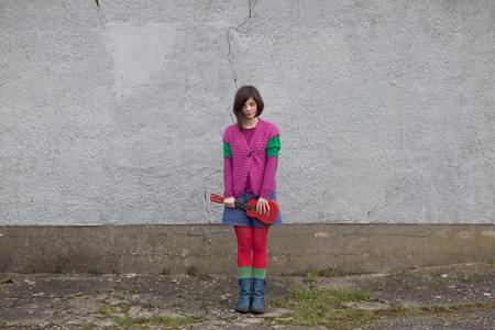 kooky: Young woman standing with ukulele