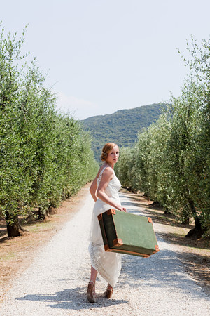 Bride carrying suitcase on country road LANG_EVOIMAGES