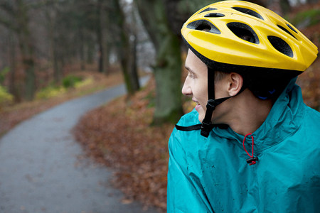 Young man wearing cycling helmet on forest path and looking over shoulder