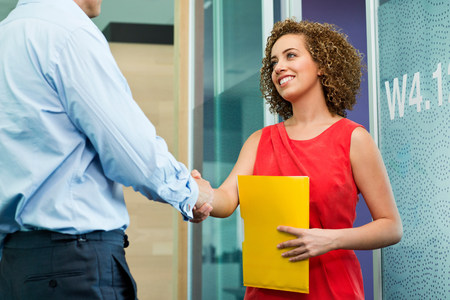 age 25 30 years: Business colleagues shaking hands in office