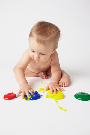 Baby putting hands in finger paints