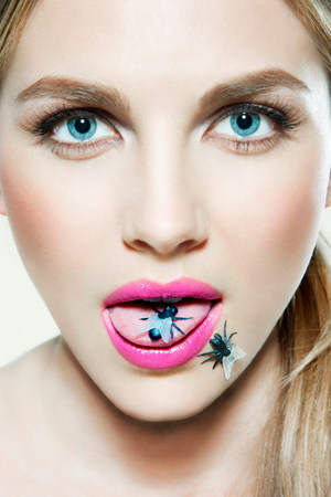 out of context: Young woman with plastic fly on tongue