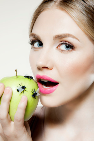 fetishistic: Young woman eating apple with flies on it LANG_EVOIMAGES