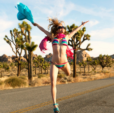 kooky: Young woman wearing bikini with arms out on desert road LANG_EVOIMAGES