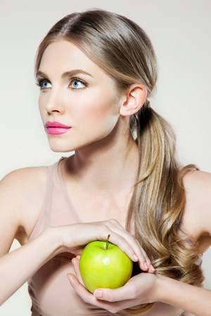 20 25 years old: Young woman holding apple