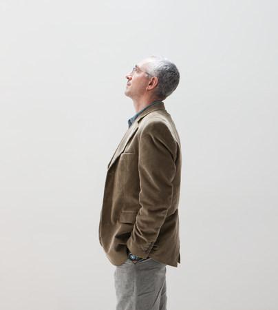 ponderous: Mature man with hands in pocket looking up,studio shot
