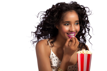 Young woman eating popcorn,studio shot LANG_EVOIMAGES