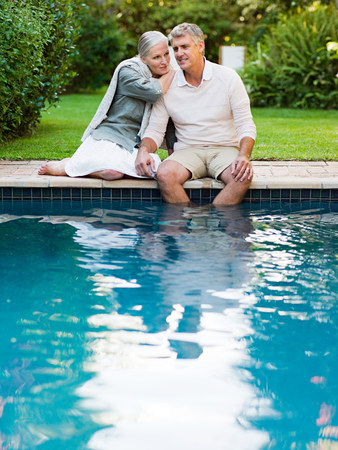 Couple sitting at poolside in garden LANG_EVOIMAGES