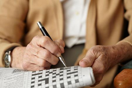 pluma de escribir antigua: Mujer mayor haciendo crucigramas LANG_EVOIMAGES