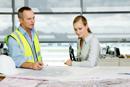 Engineer with architect looking at blueprints in office LANG_EVOIMAGES