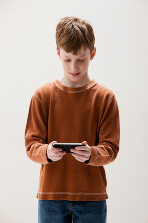 Boy in brown sweater playing hand held video game,studio shot LANG_EVOIMAGES