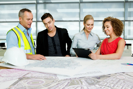Engineer with architects looking at blueprints and digital tablet in office LANG_EVOIMAGES