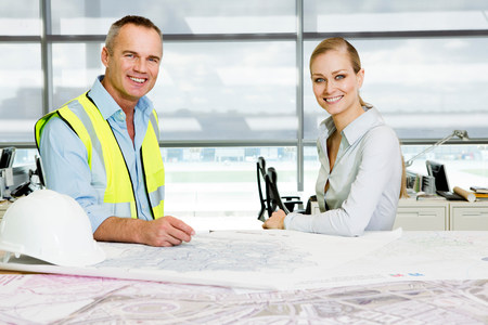 age 25 30 years: Portrait of engineer with architect at desk of blueprints in office LANG_EVOIMAGES