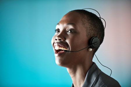 Young woman wearing telephone headset,laughing