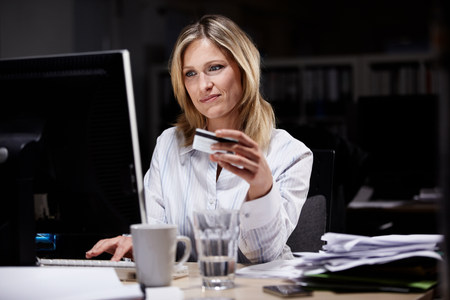 Businesswoman in dark office,using credit card online LANG_EVOIMAGES