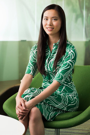 Portrait of young woman in green dress in office LANG_EVOIMAGES