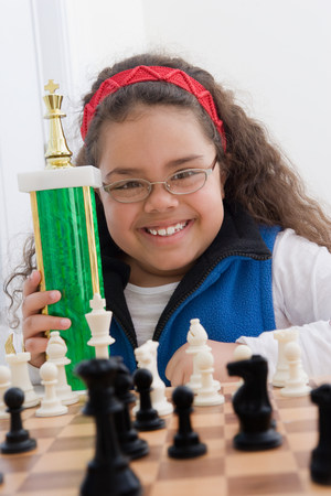 Portrait of young girl holding chess trophy LANG_EVOIMAGES