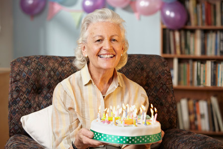 Senior woman holding birthday cake,portrait LANG_EVOIMAGES