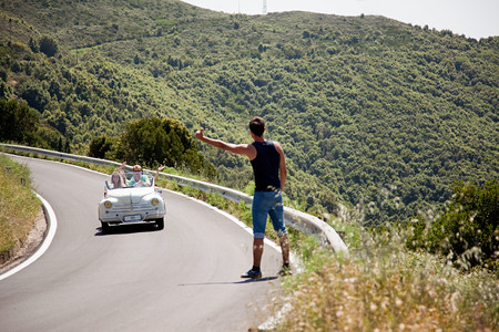 Hitchhiker waiting for convertible car to stop
