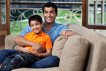 Portrait of father and son on a sofa LANG_EVOIMAGES