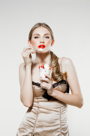 unhealthiness: Young woman eating strawberries and cream