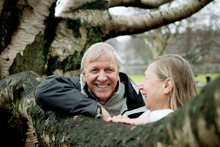 65 69 years: Senior couple leaning against tree,smiling