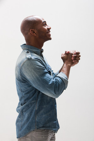 hopefulness: African American man with hands clasped,studio shot
