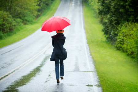 Woman on empty road with red umbrella