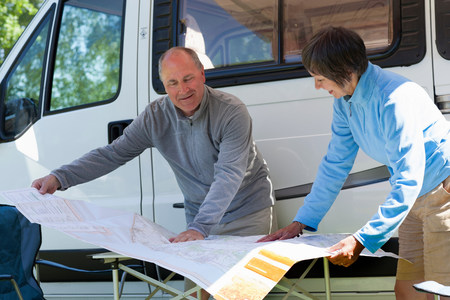 60 64 years: Couple looking at map outside campervan LANG_EVOIMAGES