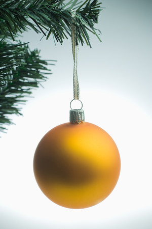 Yellow christmas bauble hanging on tree LANG_EVOIMAGES