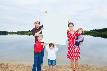 Family by lake,holding a blank sign