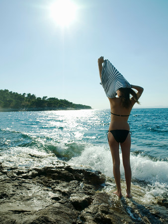 undoing: Young woman taking off t-shirt by the sea
