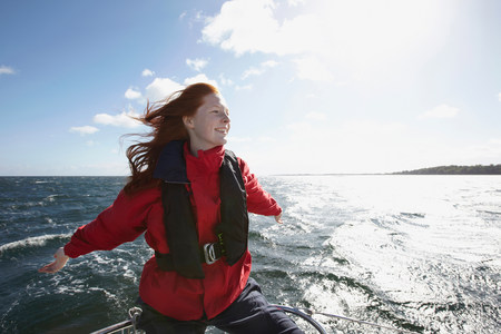 liberating: Young woman sailing with arms out