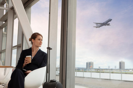 hopefulness: Businesswoman drinking coffee in airport LANG_EVOIMAGES