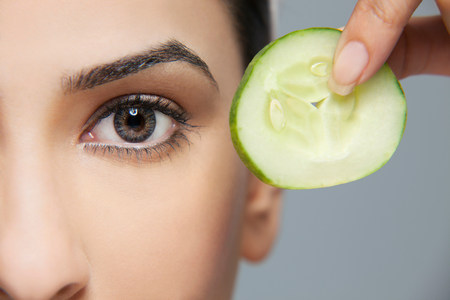 indian subcontinent ethnicity: Woman with a cucumber next to her eye
