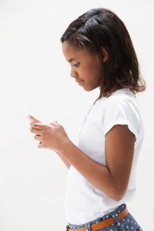 African American girl using cellphone,studio shot LANG_EVOIMAGES