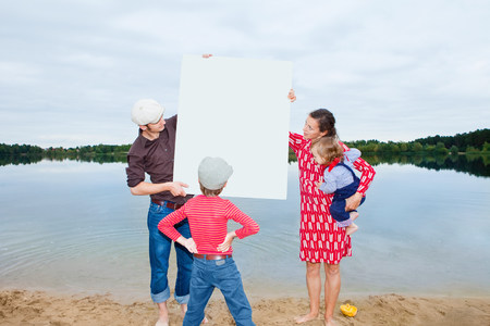 Family by lake,looking at a blank sign