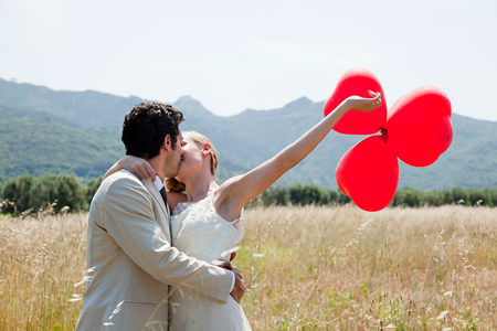 19 year old boy: Newlyweds kissing in field with red heart shape balloons