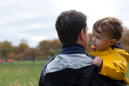 Father holding young son in park
