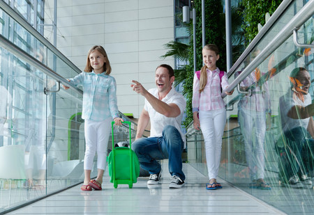6 7 year old: Father and daughters with luggage in airport
