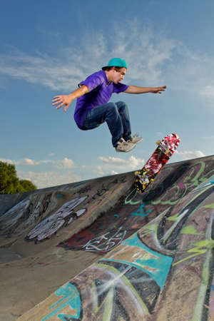 Skateboarder jumping on half pipe