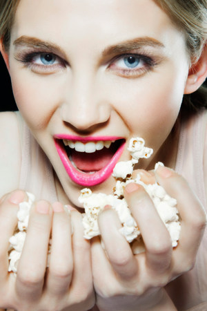 unfit: Young woman eating popcorn LANG_EVOIMAGES